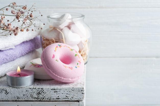 Composizione spa con ciambelle bomba da bagno e fiori secchi su fondo rustico in stile monocromatico.