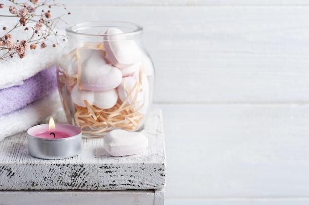 Composizione spa con cuori di bomba da bagno e fiori secchi su fondo rustico in stile monocromatico. candele e sale. trattamenti di bellezza e relax