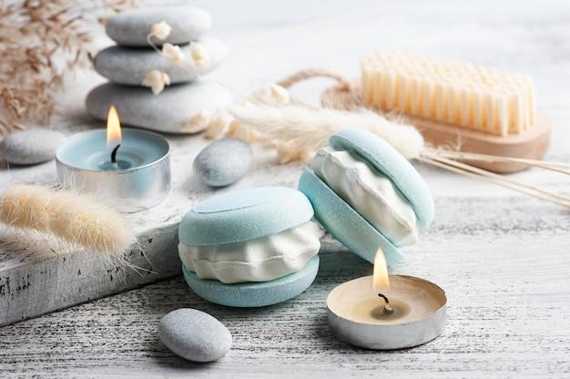 Composizione spa con amaretto bomba da bagno e fiori secchi sul tavolo rustico in stile monocromatico. candele e sale. trattamenti di bellezza e relax