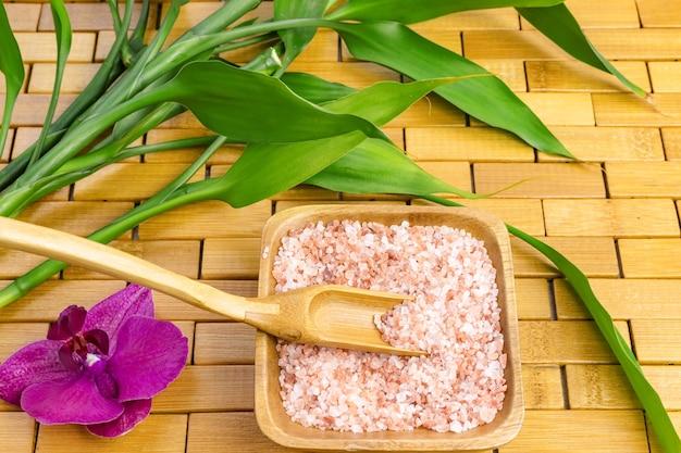 Composizione spa con sale da bagno con foglie di bambù e orchidea viola sul tappeto di legno