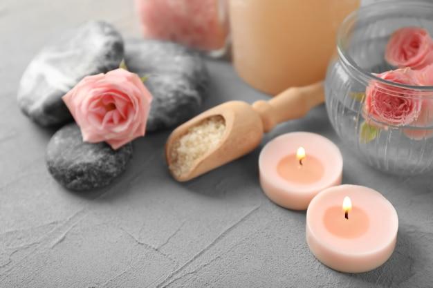 Composizione spa con candele e fiori sul tavolo grigio