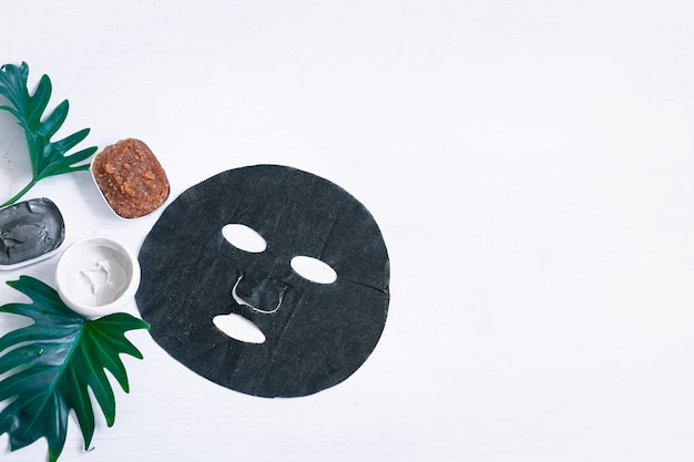 Composizione spa con articoli per la cura del viso con maschera nera e foglie. il moderno concetto di spa e prodotti di bellezza.