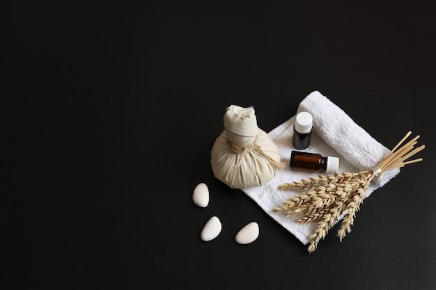 Composizione spa con borsa per massaggi alle erbe, rametto di grano, oli e luffa su sfondo nero, spazio copia.