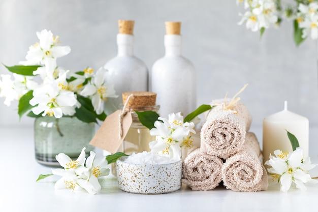 Composizione nella stazione termale con i fiori del gelsomino sulla fine bianca della tavola su.