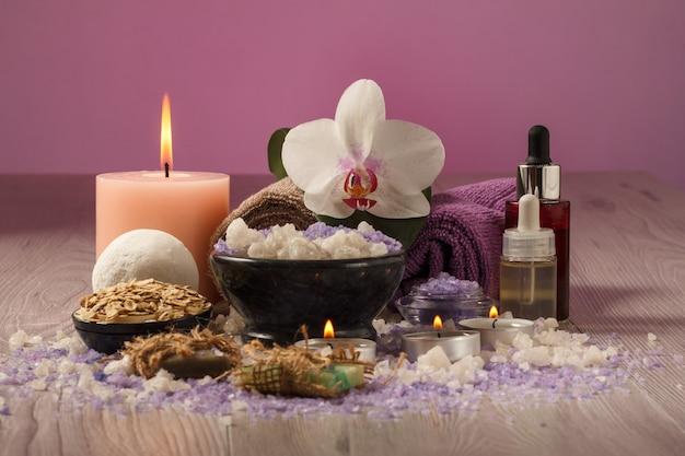 Composizione spa con fiori di orchidea, ciotola con sale marino, bottiglie con olio aromatico, sapone, scrub, candele e asciugamani su tavola di legno e sfondo rosa