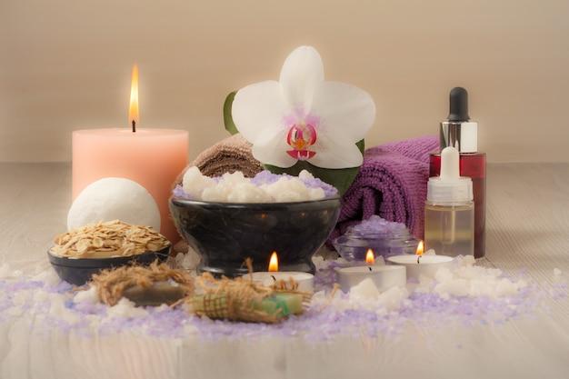 Composizione spa con fiori di orchidea, ciotola con sale marino, bottiglie con olio aromatico, sapone, scrub, candele e asciugamani su tavola di legno