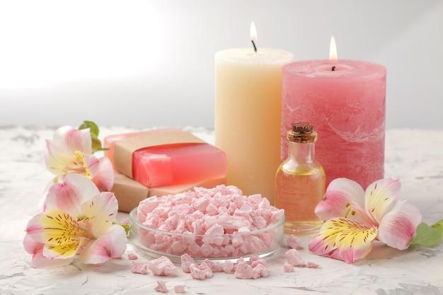 Composizione spa con sale marino, oli aromatici e sapone artigianale ai fiori. concetto di stazione termale. su uno sfondo chiaro.