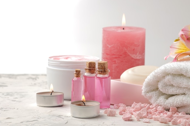 Composizione spa con sale marino, oli aromatici, asciugamani e saponi e scrub corpo. concetto di stazione termale. su uno sfondo chiaro.