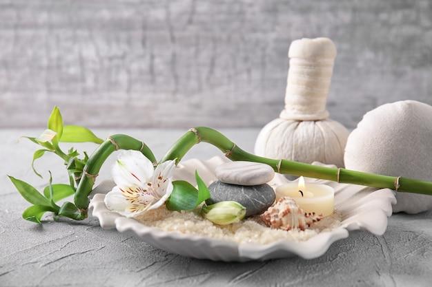 Composizione spa con sale marino, candela e pietre sul tavolo grigio