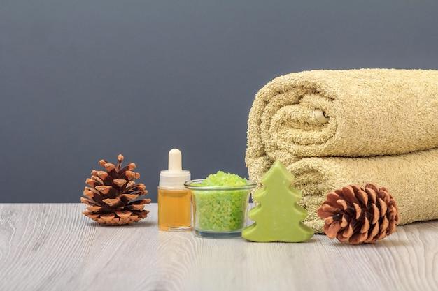 Composizione spa con un morbido asciugamano in spugna, una bottiglia con olio aromatico, una ciotola con sale marino e coni sullo sfondo grigio