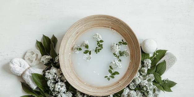Composizione spa con acqua per trattamenti estetici e fiori freschi flat lay