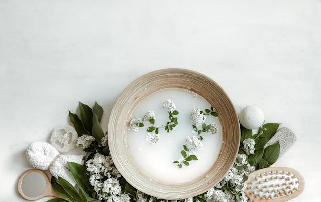 Composizione spa con acqua per trattamenti estetici e fiori freschi