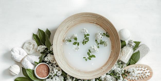 Composizione spa con acqua per trattamenti estetici e fiori freschi.