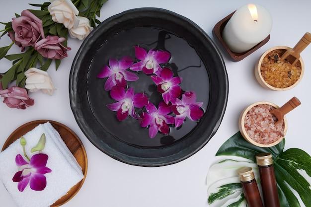 Concetto di spa. concetto di bellezza e moda con set spa. acqua profumata di fiori. rilassamento e zen, spa impostazione distesa con ciotola, sale da bagno e fiori, asciugamano e sapone naturale. vista dall'alto.
