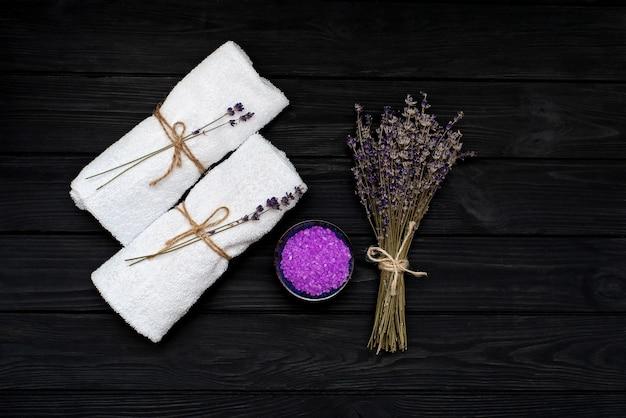 Concetto spa. sale di lavanda per un bagno rilassante, asciugamani bianchi e fiori di lavanda asciutti su un fondo di legno nero. aromaterapia piatto disteso.
