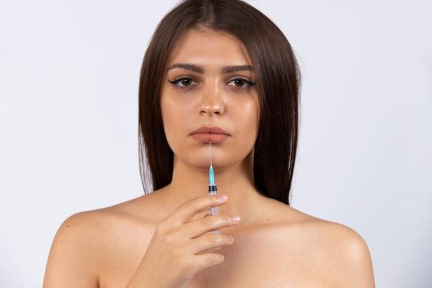 Concetto di spa, volto femminile triste, labbra e iniezioni di cosmetici. cosmetologia, spa, bellezza. foto sul muro bianco. foto di alta qualità