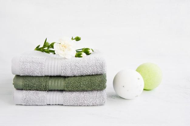 Concetto di stazione termale. due bombe da bagno e asciugamani da bagno decorati con fiori di garofano su sfondo chiaro. copia spazio per il testo