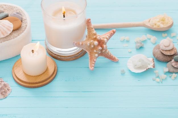Concetto della stazione termale con le candele su fondo di legno blu