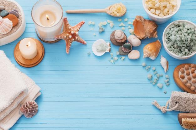 Concetto della stazione termale con le candele sulla tavola di legno blu