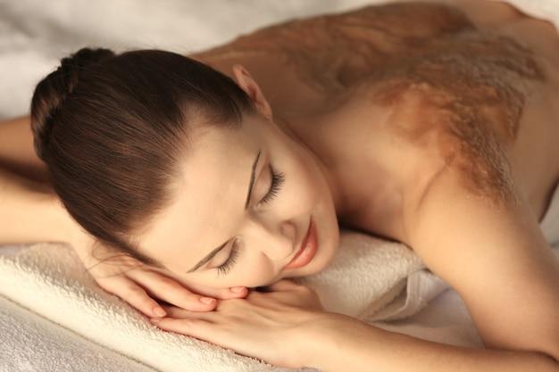 Concetto di stazione termale. giovane donna che si rilassa sul lettino per massaggi con uno scrub nutriente sulla schiena