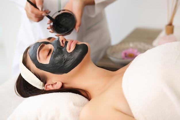 Concetto di spa. giovane donna con maschera facciale nutriente nel salone di bellezza, primi piani