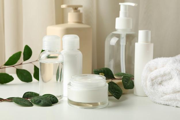 Prodotti cosmetici spa e foglie sul tavolo bianco