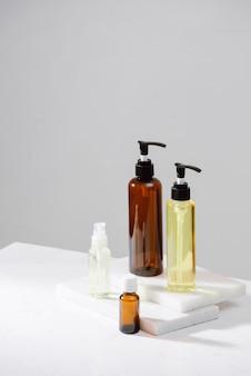 Cosmetici termali in bottiglie di vetro marrone sul tavolo di cemento grigio. copia spazio per il testo. blogger di bellezza, terapia del salone, mockup del marchio, concetto di minimalismo