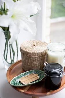 Elementi della stazione termale su un vassoio di legno con un fiore