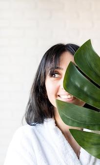 Maschera facciale spa. spa e bellezza. felice bella bruna donna mediorientale che indossa accappatoi in possesso di una foglia verde monstera davanti al viso