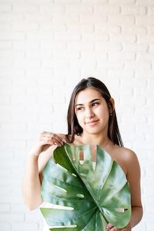 Maschera facciale spa. spa e bellezza. felice bella donna bruna indossando asciugamani da bagno tenendo una foglia di monstera verde davanti al viso