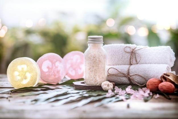 Sapone artigianale spa con asciugamani bianchi e sale marino, composizione su foglie tropicali, fondo in legno