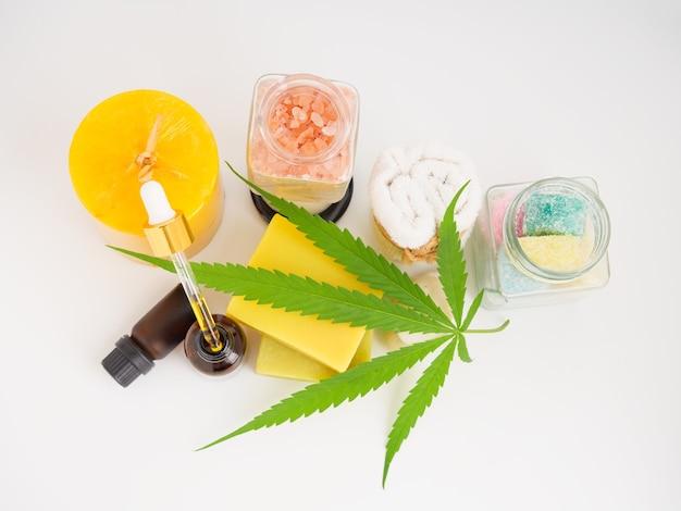 Spa prodotti estratti di canapa con saponetta in foglia di cannabis lozione all'olio di cbd e pietra dell'asciugamano bianco sale rosa himalayano su sfondo bianco