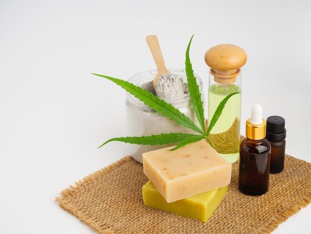Spa prodotti di estratto di canapa con foglia di cannabis saponetta cbd olio lozione e maschera di fango su tela, sacco su sfondo bianco