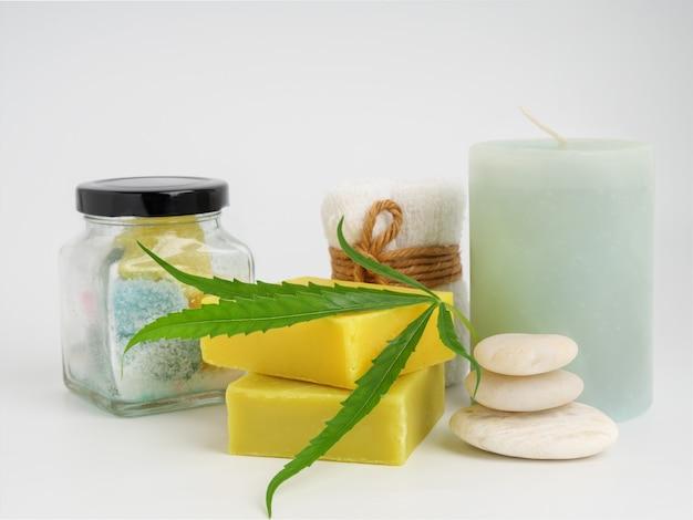 Prodotti di estratto di canapa termale con saponetta in foglia di cannabis e pietra bianca per asciugamani su sfondo bianco