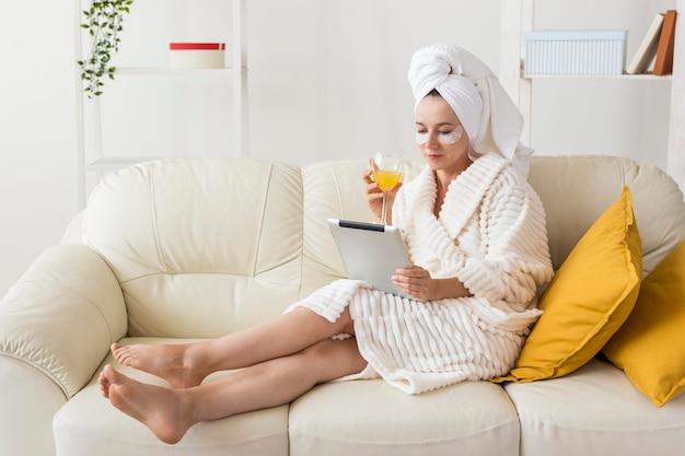 Spa a casa donna che beve succo di frutta sano seduto sul divano