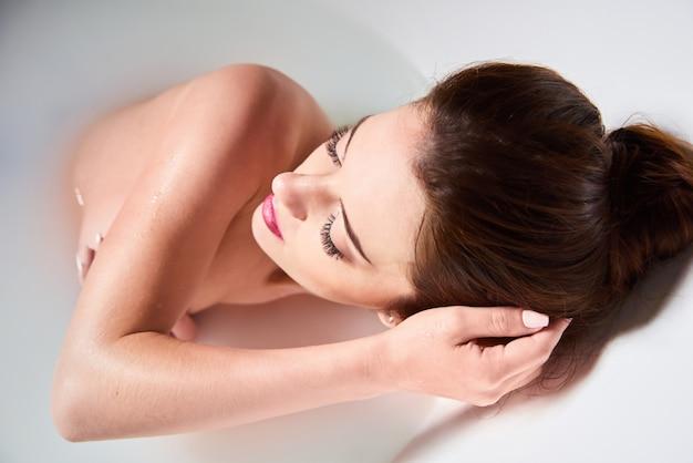 Stazione termale a casa - la donna si rilassa in bagno. bella donna caucasica in vasca con latte. una ragazza attraente che si distende nel bagno su priorità bassa chiara