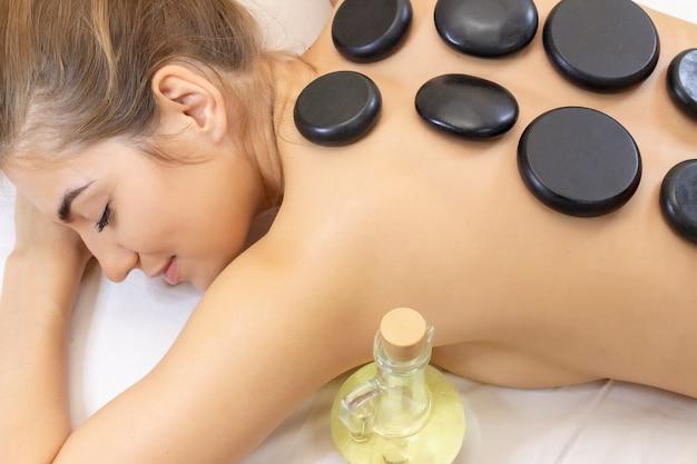 Spa massaggio con pietre calde per donna sulla schiena con pietre