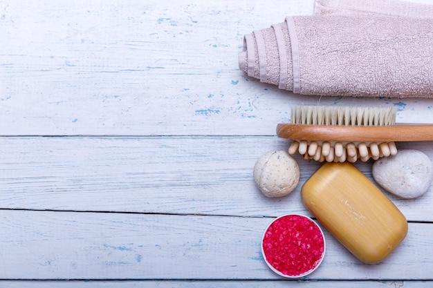 Kit spa o concetto set con prodotti biologici naturali sul tavolo di legno bianco. barra di sapone e liquido. sale rosa aromaterapico. vista dall'alto con spazio di copia.