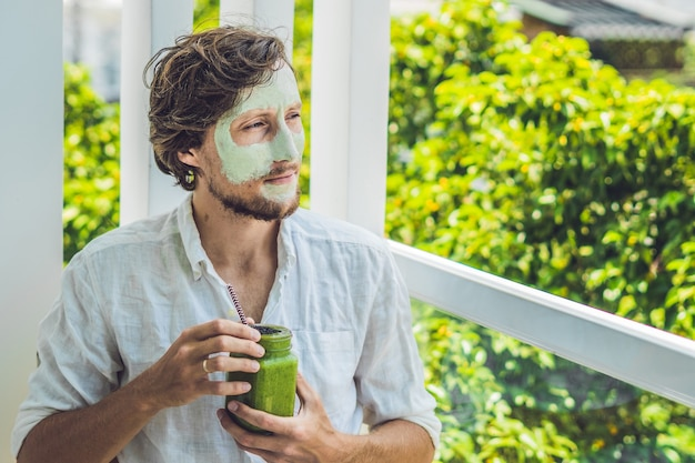 Uomo della stazione termale che applica maschera facciale all'argilla verde. trattamenti di bellezza. frullato verde fresco con banana e spinaci con cuore di semi di sesamo. amore per un concetto di cibo crudo sano. concetto di disintossicazione