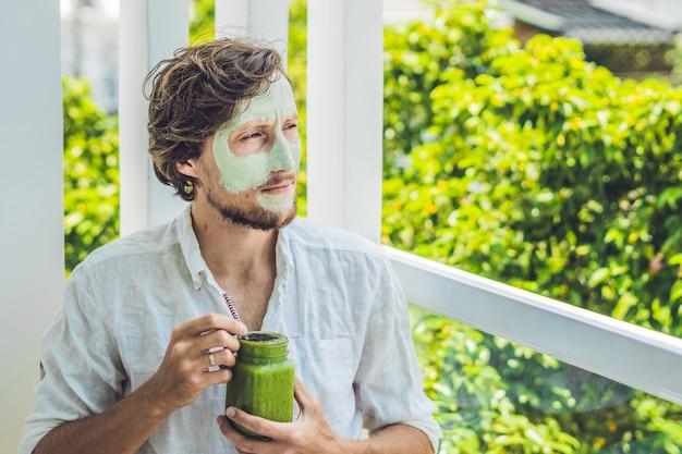 Uomo della stazione termale che applica maschera facciale all'argilla verde.