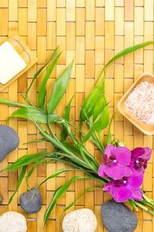 Massaggio termale concetto piatto giaceva con foglie di bambù, pietre e fiori sulla stuoia di legno