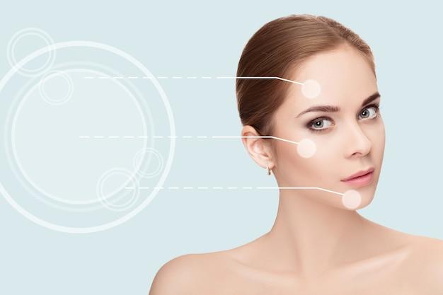 Spa ritratto di donna giovane, bella e naturale con frecce tratteggiate sul viso su sfondo blu. avvicinamento. medicina e cura della pelle