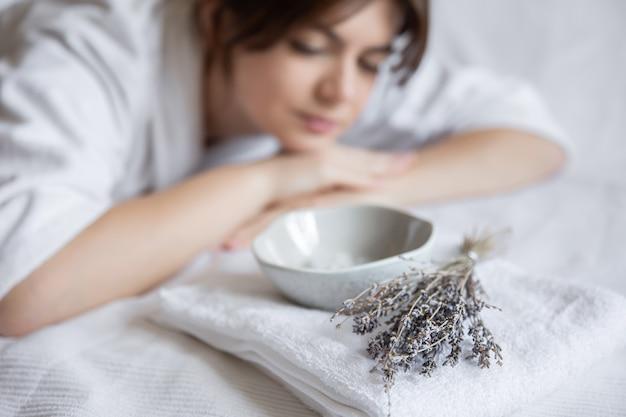 Procedura spa nel salone, una giovane donna in una veste bianca giace, una ciotola con una maschera per il viso e lavanda.