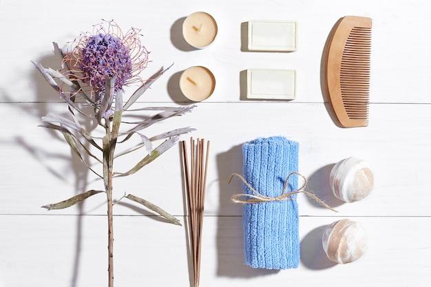 Prodotti termali sali da bagno fiori secchi sapone alla lavanda candele e asciugamano piatti adagiati su legno bianco backgro