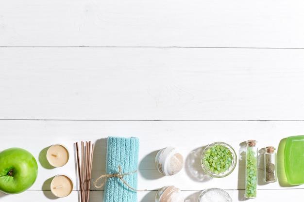 Prodotti termali sali da bagno sapone candele e asciugamano piatto adagiato su sfondo di legno bianco vista dall'alto