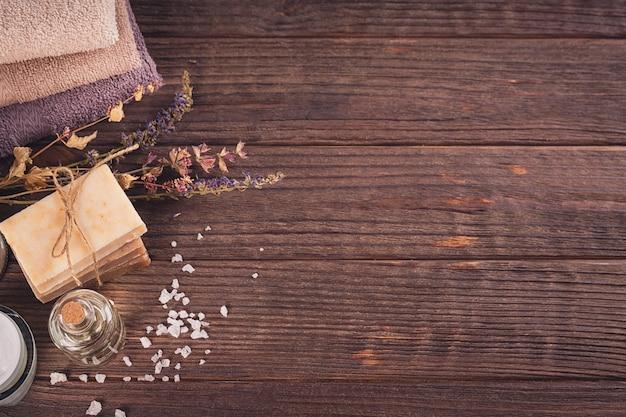 Prodotti termali per la cura del viso e del corpo. sale marino naturale, sapone fatto in casa, olio da massaggio e asciugamani colorati. spa e concetto di cura del corpo. vista dall'alto con spazio per il testo