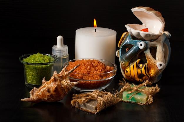 Prodotti termali con sapone fatto a mano, ciotole con sale marino, bottiglia con olio aromatico, candele e conchiglia su sfondo nero