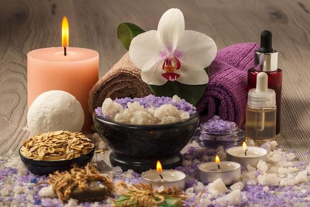 Prodotti termali con fiori di orchidea, ciotola con sale marino, bottiglie con olio aromatico, sapone, scrub, candele e asciugamani su tavola di legno