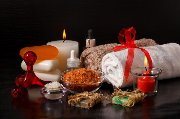 Prodotti termali con sapone, ciotole con sale marino, bottiglie con olio aromatico, candele e asciugamani su sfondo nero