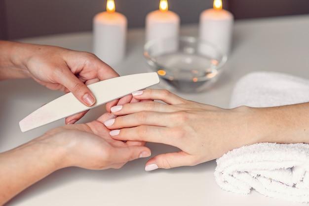 Salone spa. mani di bella donna che hanno limatura delle unghie con lima per unghie dal manicure. procedura cosmetica, manicure sulla mano femminile